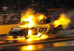 Ashley Force Hood's Mustang is engulfed in a shower of sparks during a blow-up in Friday's qualifying sessions at Maple Grove Raceway.