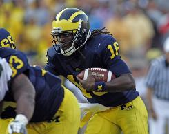 Michigan quarterback Denard Robinson, looking for an open running lane during the Wolverines' loss to Michigan State on Saturday, is second in the nation in rushing yards with 165.2 a game.