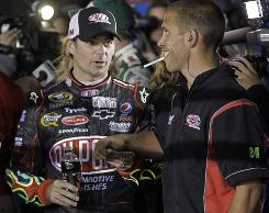 Jeff Gordon, left, talks to a crewmember after turning the fastest lap in Thursday qualifying at Charlotte Motor Speedway.