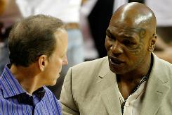 Sportscaster Jim Gray (L) and formerheavyweight champion Mike Tyson talk during a preseason game between the Los Angeles Lakers and the Sacramento Kings on Oct. 13.