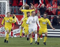 Columbus Crew goalkeeper William Hesmer (wearing white) celebrates his game-tying goal, the second score by a goalie in MLS history. The Crew tied Toronto FC 2-2.