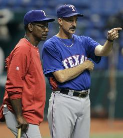 Rangers pitching coach Mike Maddux, right, talks with manager Ron Washington during a practice for the American League Division Series.