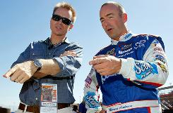 Marcos Ambrose speaks with 'Amazing Race' host Phil Keoghan during practice at Auto Club Speedway on Oct. 9.