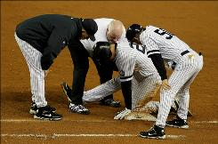 The Yankees' Mark Teixeira is tended to by manager Joe Girardi, left, after he was injured running to first base in the fifth inning.