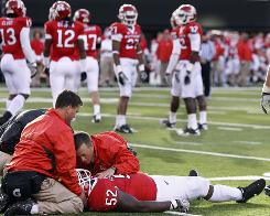 Rutgers defensive tackle Eric LeGrand (52) is treated on the field after colliding with Army's Malcolm Brown (23) as he tried to make the tackle during the second half of a football game Saturday, 