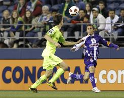 Saprissa's Javier Loaiza, right, and the Sounders' Alvaro Fernandez vie for the ball during the first half Tuesday of their CONCACAF Champions League soccer match in Seattle.