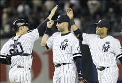 From left to right, the Yankees' Jorge Posada, Derek Jeter and Robinson Canoe celebrate after beating the Rangers 7-2 in Game 5 of the ALCS.