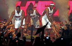 From left, Dwyane Wade, Chris Bosh and LeBron James are introduced in Miami on July 9.