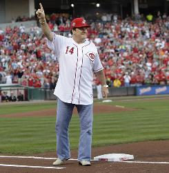 Former Cincinnati Reds great Pete Rose stands on first base as he acknowledges the crowd during ceremonies celebrating the 25th anniversary of Rose breaking Ty Cobb's hit record.