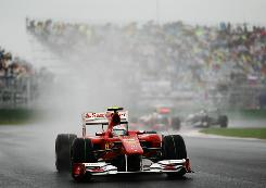 Fernando Alonso's Ferrari leads the field in a soggy Korean Grand Prix