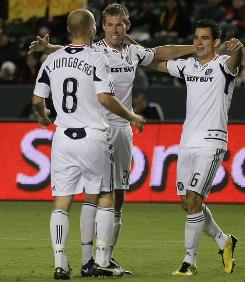 The Fire's Brian McBride, center, celebrates Freddie Ljunberg's goal with Marco Pappa during the second half against Chivas USA. McBride scored in his final MLS game, giving him 80 goals in 220 career games.