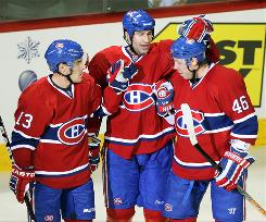 Montreal Canadiens' Mike Cammalleri, left, celebrates with teammates Roman Hamrlik and Andrei Kostytsyn, right, in the second period after scoring. Kostystsyn would score the game-winning goal in overtime.