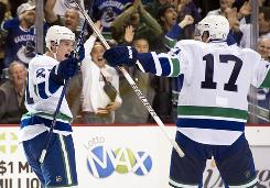 Mason Raymond, left, celebrates with Canucks teammate Ryan Kesler after scoring the game-winning goal in overtime to lift Vancouver to a 4-0-1 home record.