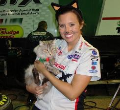 Ashley Force Hood and one of her cats get in the Halloween holiday spirit at the team's race shop.