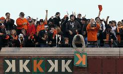 "A fan hangs a ""K"" after Madison Bumgarner, one of the Giants four home-grown starting pitchers, strikes out another batter. San Francisco has rebuilt its team around a stronger farm and scouting system."