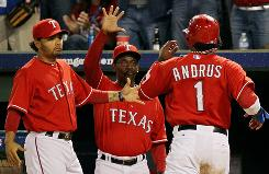 Rangers manager Ron Washington, center, preaches an aggressive style of play embraced by his players, including shortstop Elvis Andrus.