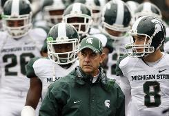 Michigan State coach Mark Dantonio was on the field Saturday, leading his Spartans to victory vs. Northwestern. Dantonio suffered a heart attack in September and had been coaching from the press box.