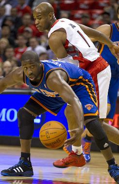 New York Knicks guard Raymond Felton gathers up a loose ball from Toronto Raptors guard Jarrett Jack during first-half action in Toronto.