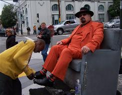 Longtime Giants fan Jeremy Lassen, 40, wearing an orange zoot suit, gets his shoes shined a block from AT&T Park by Monroe Greene, 71. The Giants colors are black, orange and cream.