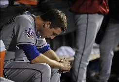Rangers relief pitcher Derek Holland gathers his thoughts in the dugout after giving up three walks to three batters during the Giants' seven-run eighth inning in Game 2.