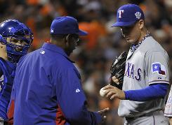 Rangers manager Ron Washington relieves Derrek Holland in the eighth inning after he walked three consecutive batters to force three.