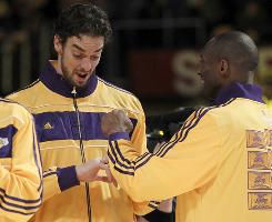 The  Lakers' Pau Gasol and Kobe Bryant look at their NBA championship rings on Tuesday.
