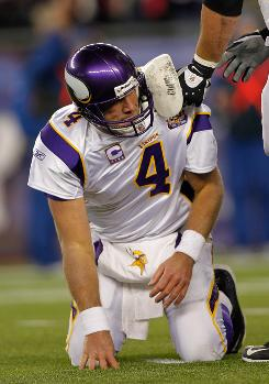 Vikings quarterback Brett Favre is helped off the ground after being injured during the second half against the Patriots on Sunday. New England won 28-18.