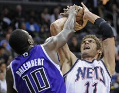 Sacramento Kings' Samuel Dalembert blocks a shot by New Jersey Nets' Brook Lopez during the first quarter on Friday.