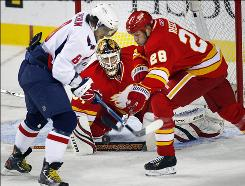 The Capitals' Alex Ovechkin, battling the Flames' Robyn Regehr for the loose puck in front of goalie Miikka Kiprusoff, scored twice in a 12-second frame to help propel Washington to victory.