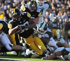 Iowa running back Adam Robinson dives into the end zone for a touchdown in the grasp of Michigan State defensive tackle Anthony Rashad White during the second quarter.