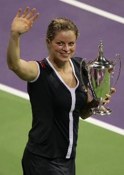Kim Clijsters of Belgium celebrates with the trophy after defeating Caroline Wozniacki 6-3, 5-7, 6-3 to win the season-ending WTA Championships on Sunday in Doha, Qatar.