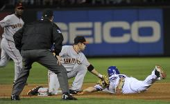 The Giants' Freddy Sanchez, left, tagging Josh Hamilton in the fourth inning, let his defense do his talking Sunday night.
