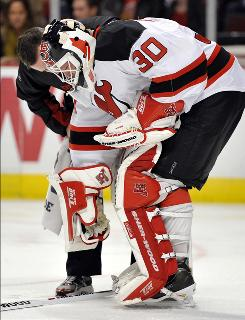 A Devils trainer tends to Martin Brodeur after the goalie suffered a bruised right elbow during the second period against the Blackhawks.