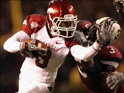 Arkansas' Joe Adams tries to get past South Carolina's Akeem Auguste as the Razorbacks handed the Gamecocks their worst loss at home since a 2005 defeat courtesy of Auburn.