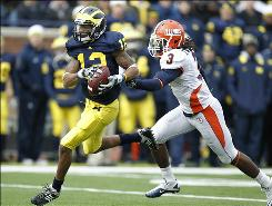 Michigan wideout Roy Roundtree, getting past Illinois defender Tavon Wilson during the second quarter, set a Michigan record with nine catches for 246 yards and two touchdowns.