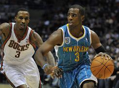 Milwaukee Bucks' Brandon Jennings guards New Orleans Hornets' Chris Paul, who drives to the basket during the first half on Saturday.