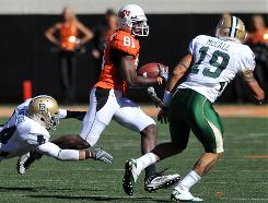 Oklahoma State wide receiver Justin Blackmon attempts to elude a tackle by Baylor safety Byron Landor (14) and linebacker LeQuince McCall (19) during the second half.