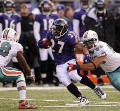 Ravens running back Ray Rice runs between Dolphins defenders Karlos Dansby, left, and Koa Misi during the second half. Rice's 180 yards from scrimmage helped the Ravens improve to 6-2.