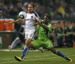 Eddie Lewis (6) of the Los Angeles Galaxy and Sanna Nyassi (23) of Seattle Sounders FC vie for the ball in the first half of the MLS Western Conference semifinal match on Sunday in Carson, Calif.