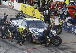 Members of Jeff Gordon's crew attend to Jimmie Johnson's car Sunday during a pit stop at Texas Motor Speedway. The swap will remain in effect for the season's final two races, Hendrick Motorsports announced Monday.