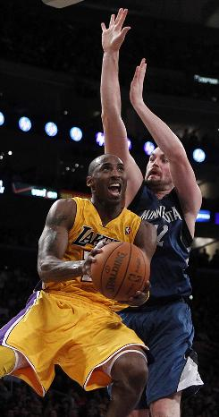 Los Angeles Lakers shooting guard Kobe Bryant drives to the basket against Minnesota Timberwolves power forward Kevin Love during the second half onTuesday.  Bryant finished with 33 points in the Lakers' eighth victory.  Love had 23.