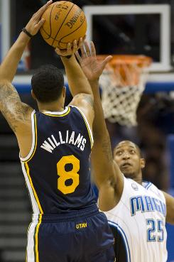 Jazz guard Deron Williams shoots a three-pointer over Magic guard Chris Duhon on Wednesday. The Jazz managed another rally just one night after stunning the Heat.