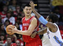 Rockets center Yao Ming, looking to pass as Nuggets center Nene Hilario (31) defends, is nursing a sprained left ankle.