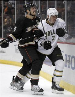 The Ducks' Ryan Getzlaf, left, checking the Stars' Nicklas Grossman during the second period, scored the go-ahead goal in the third period to help Anaheim fly to another win.