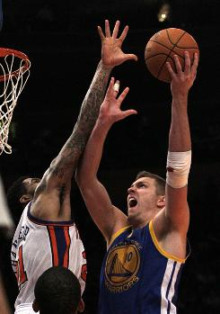 Golden State Warriors' David Lee shoots over New York Knicks' Wilson Chandler during the second half on Wednesday. His left arm is bandaged as a result of a collision with Chandler earlier in the game. Lee had surgery on the arm Friday.