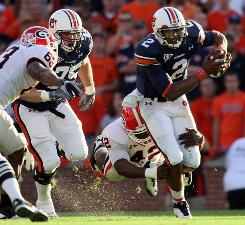 Auburn quarterback Cameron Newton fights for yards against the Georgia defense during the first half.