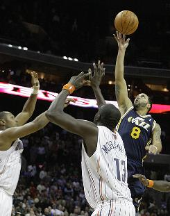 The Utah Jazz's Deron Williams (8) puts up the winning shot over the Charlotte Bobcats' Boris Diaw, left, and Nazr Mohammed (13) during the second half on Saturday. It was the fifth straight game Utah had won by coming back from double-digit deficits.