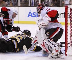 Senators golaie Brian Elliott keeps an eye on fallen Bruin Tyler Wheeler during second-period play in Boston.