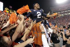 Auburn's Cameron Newton reacts with fans after a 49-31 win over Georgia at Jordan-Hare Stadium in Auburn, Ala., on Saturday. Newton remains elgible to play amid an NCAA investigation over academic fraud allegations and possible NCAA violations.