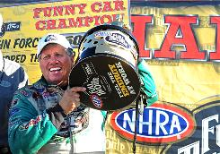 John Force celebrates after clinching the Funny Car championship during the Auto Club Finals at Pomona, Calif.